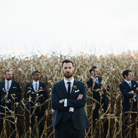 Grooms party wearing INDOCHINO suits standing in a corn field.
