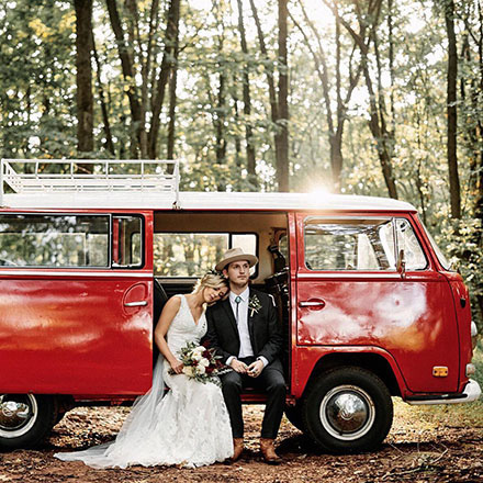 Bride and groom sitting in a vintage red van.