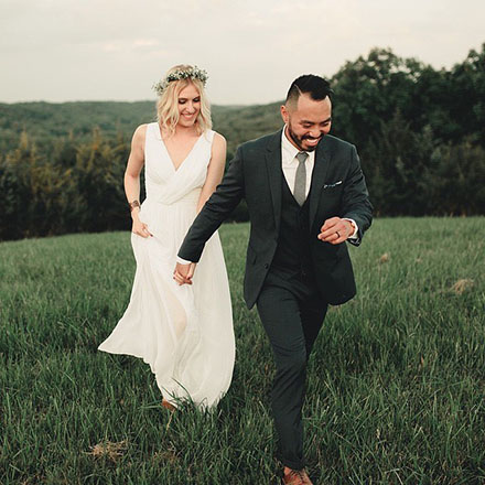 Bride and groom running down a lush green field.