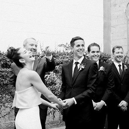 Bride and groom holding hands and sharing a laugh in front of officiant and groomsmen.