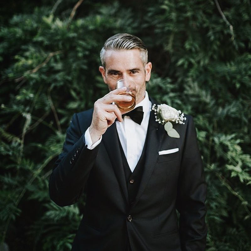 Groom wearing a black INDOCHINO suit standing in front of lush green background with drink in hand.