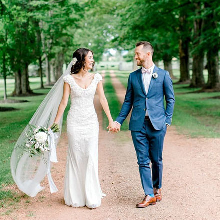 Newlyweds walking hand in hand down a garden with lush trees in the background.