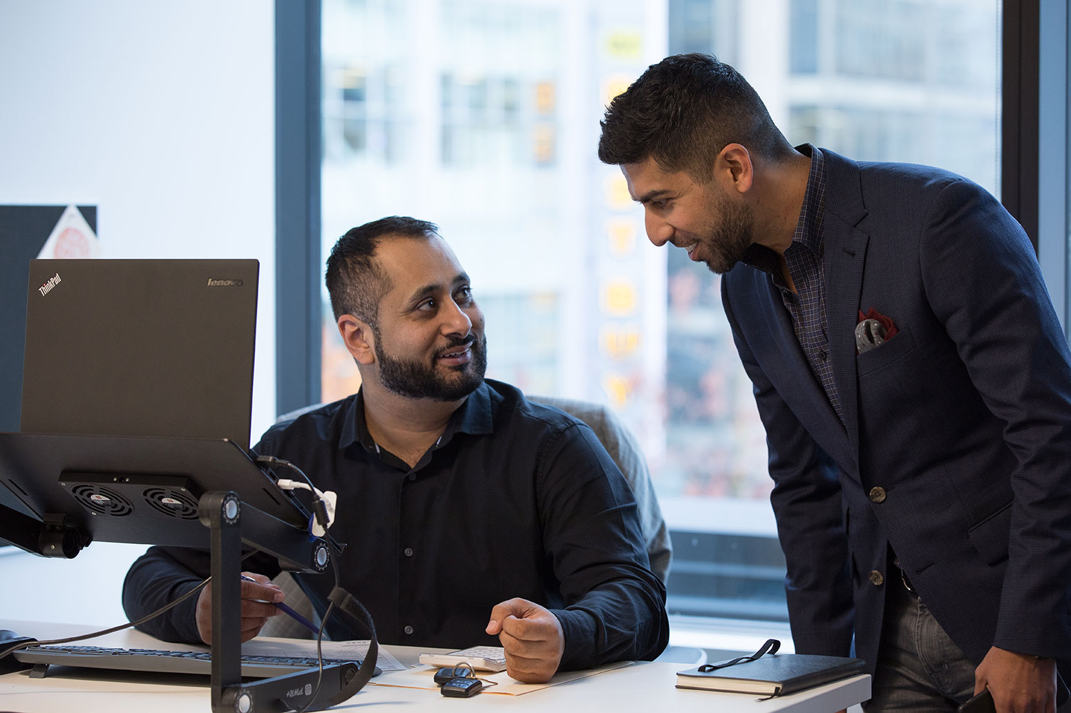 Two employees having a conversation at INDOCHINO headquarters.