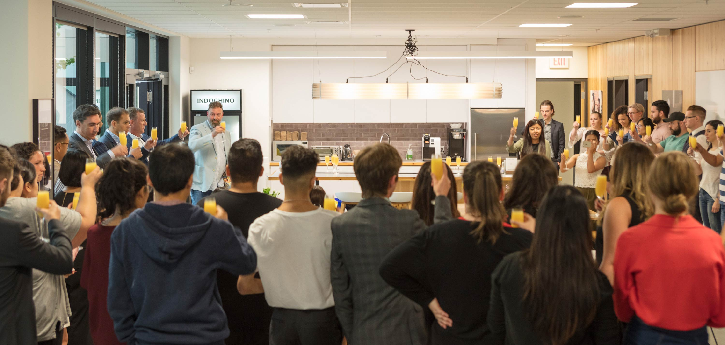 INDOCHINO employees raising a toast in the luchroom at headquarters.