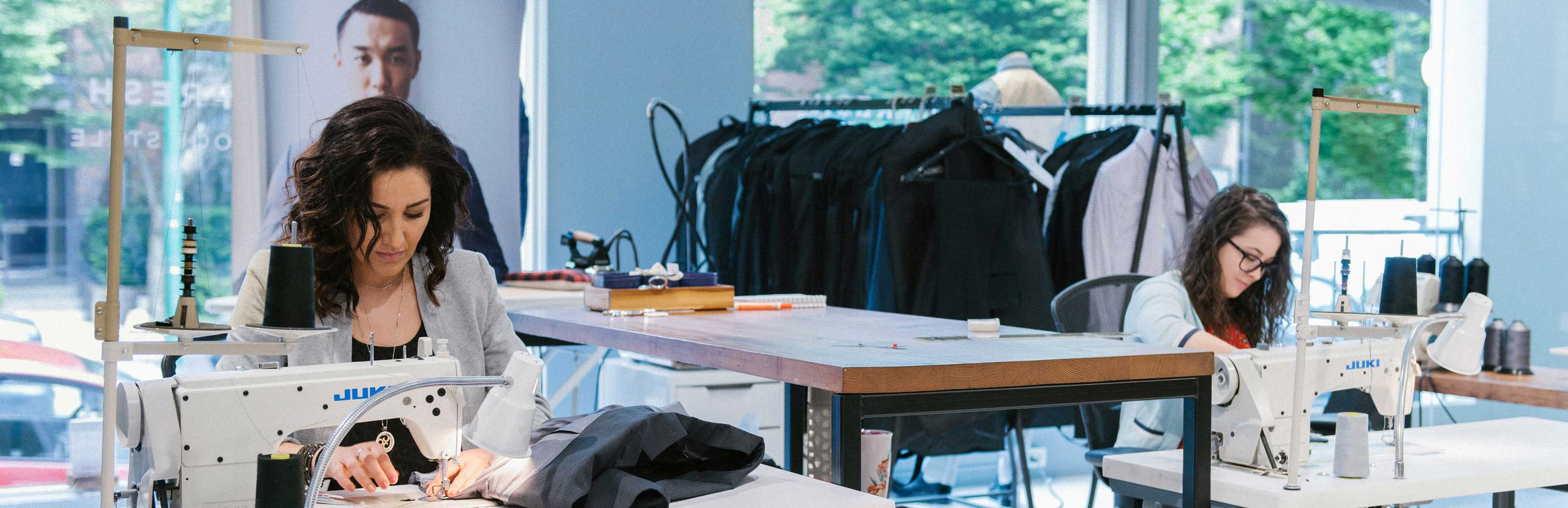 Two in-house tailors working on alterations.