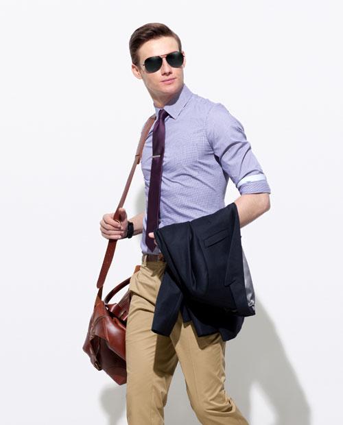 A man modeling khaki pants and a blue checkered shirt.