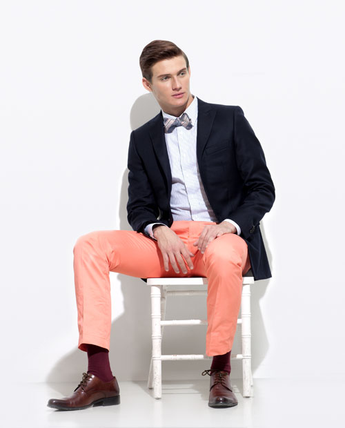 A seated man modeling a navy blazer, a blue pin-striped shirt, salmon pants and a bow tie.