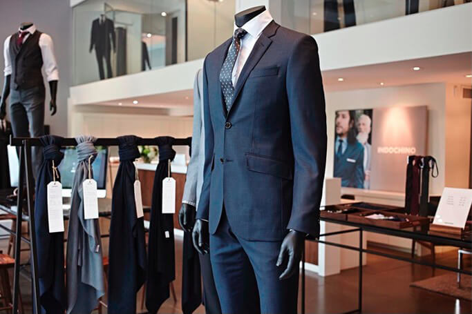 A navy suit on display in an INDOCHINO showroom.